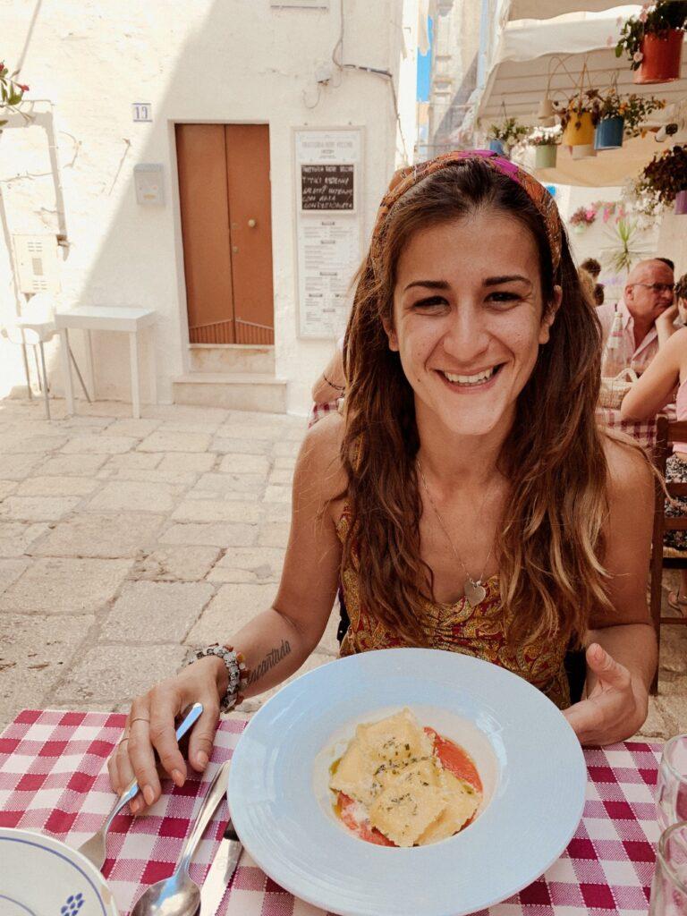 ragazza che sorride con un piatto di pasta davanti